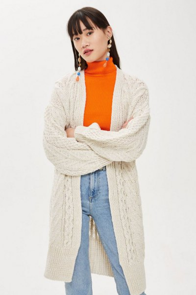 Cream-colored long knitted cardigan with an orange sweater and mom jeans