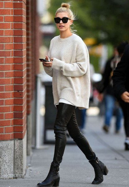 Cream-colored oversized knitted sweater with black leather gaiters
