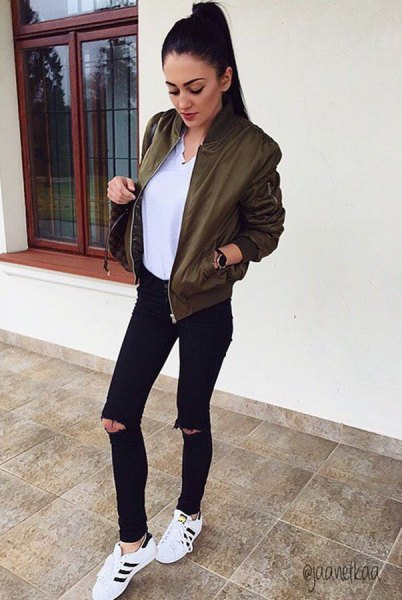 olive green bomber jacket with white blouse with V-neck and black jeans