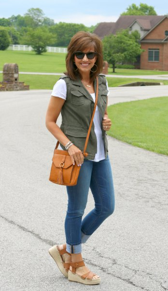 Olive green utility waistcoat with a white t-shirt and skinny jeans with cuffs