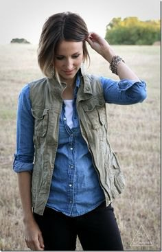 olive green vest with light blue chambray shirt and dark jeans