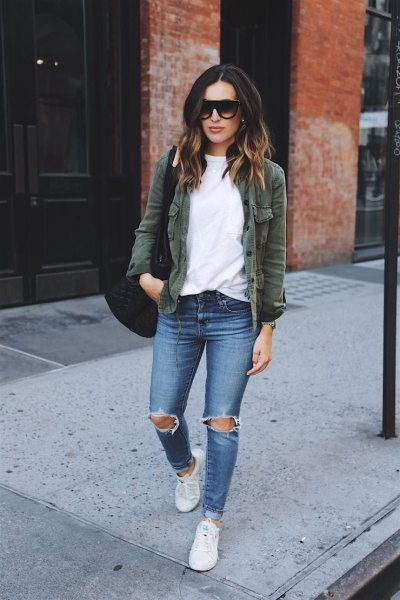 Olive green jacket with a white sweatshirt and ripped blue jeans