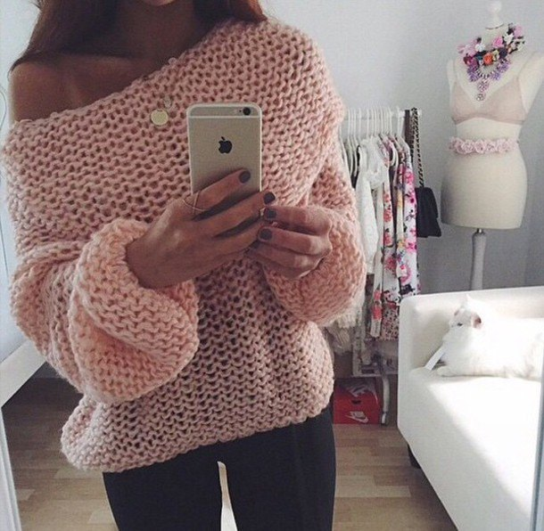 a pale pink chunky one shoulder sweater and black skinny jeans