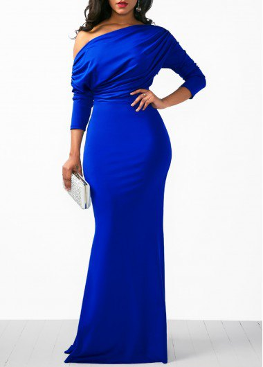 A strapless royal blue long-sleeved dress with a white clutch wallet