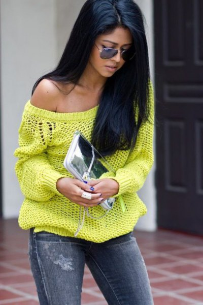 a shoulder yellow sweater with jeans and a silver clutch handbag