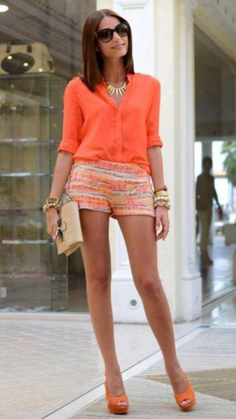 orange and white printed mini shorts and gold statement chain