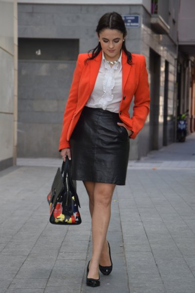 orange blazer jacket with white frilled blouse and black leather mini skirt
