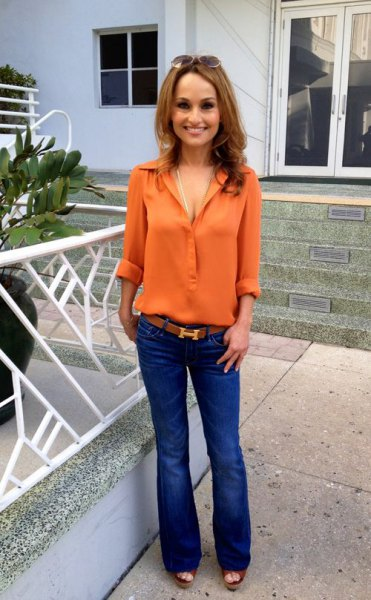 orange chiffon shirt with buttons and blue flared jeans