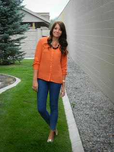 orange shirt with buttons, blue slim fit jeans and metallic shoes