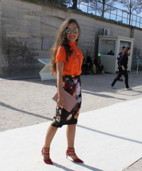orange short-sleeved shirt with buttons and black midi skirt with floral pattern