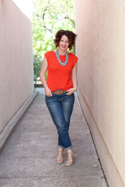 orange blouse with cap sleeves, jeans with cuffs and brown belt
