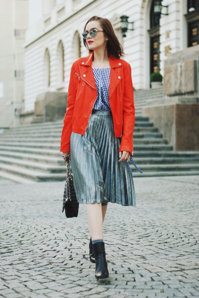 orange leather jacket with checked blouse and silver pleated skirt