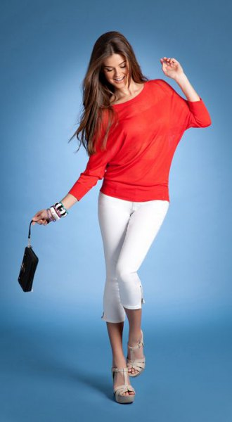 orange long-sleeved top with white skinny jeans