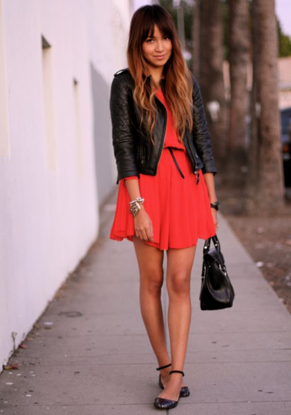 orange mini dress with black leather jacket and leather straps with ankle straps