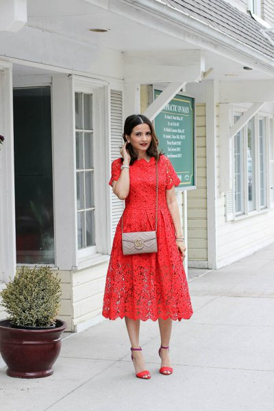 Orange short-sleeved midi lace dress with a blushing pink small purse
