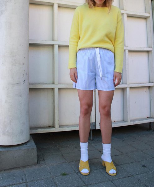 orange sweatshirt with sky blue striped knitted shorts and sandals