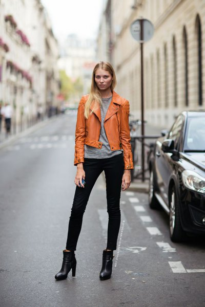 orange-brown leather jacket with gray t-shirt and black jeans