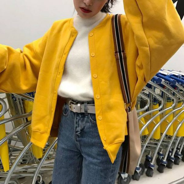 oversized lemon yellow bomber jacket with white mock-neck sweater