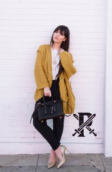 oversized mustard cardigan with black jeans and gold heels