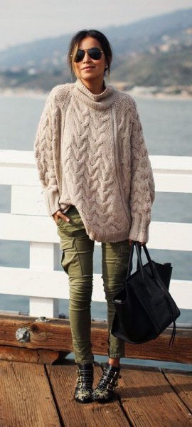 Light pink oversized cable knit sweater with green skinny cargo jeans