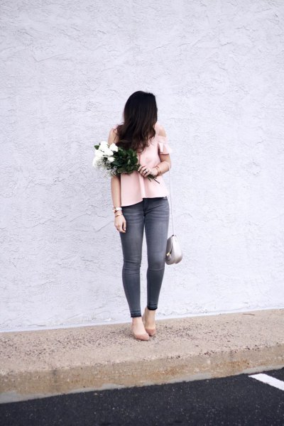 Light pink top with a cold shoulder and gray skinny jeans