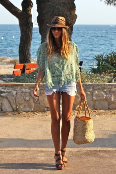 Light pink crochet top with mini denim shorts and a beach straw sack