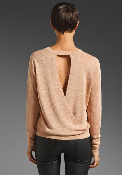 Light pink sweater with a cut out back and black skinny jeans