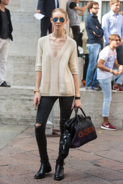 Light pink sweater with a deep V-neckline, black jeans and short boots