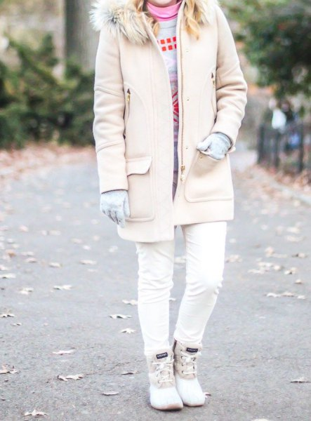pale pink long coat with a faux fur collar, skinny jeans and white duck boots