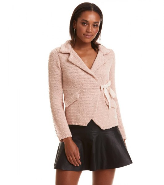 Light pink cardigan with a black mini skater leather skirt