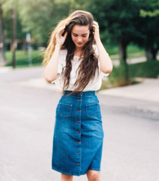 Light pink, lace, short-sleeved top with a blue, high-waisted, knee-length denim skirt