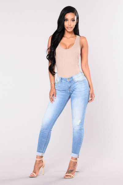 Light pink, low cut, figure-hugging tank top with sky blue, flat skinny jeans