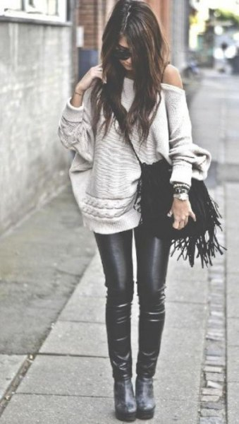 Light pink one-shoulder sweater with black leather gaiters