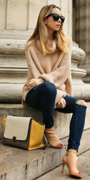 Light pink oversized knitted sweater with ripped dark jeans