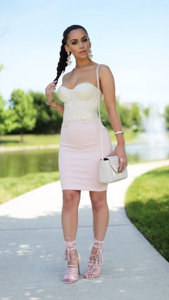 Light pink, figure-hugging mini dress with a sweetheart neckline and white lace-up sandals