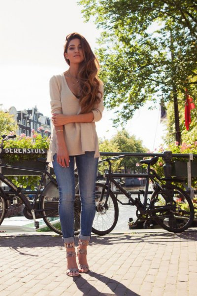 Light pink V-neck sweater and blue skinny jeans with cuffs