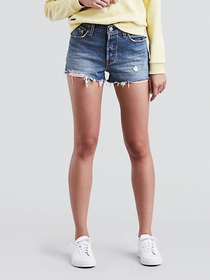 Light yellow chunky sweatshirt with blue Levis denim shorts and white sneakers