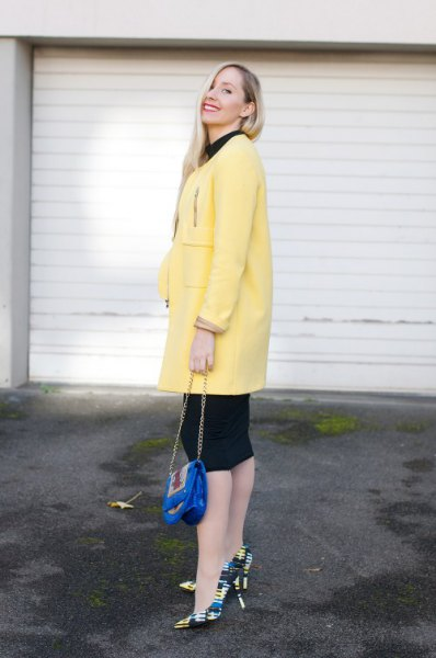 light yellow long wool coat with black knee-length shift dress