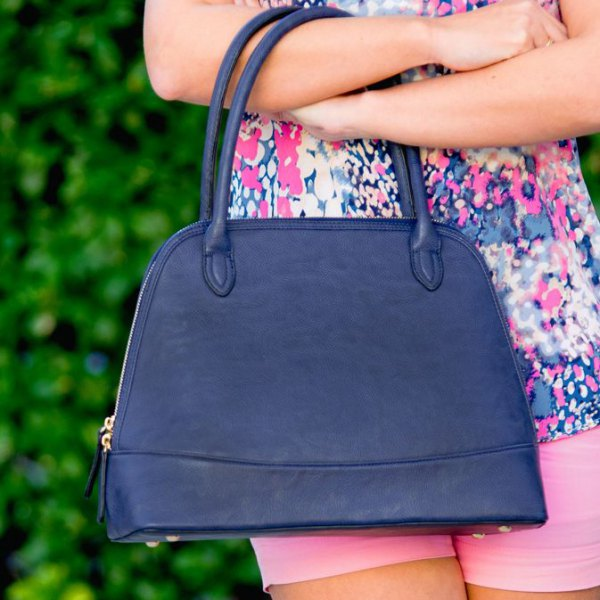 Sleeveless blouse with a pink and white floral print and a dark blue handbag