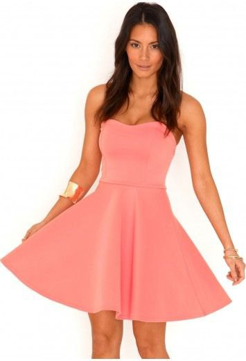 Strapless mini dress in pink and flare with a gold cuff bracelet