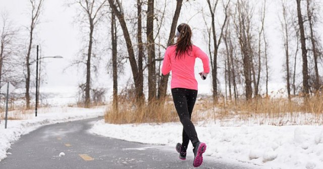 pink fitted sweatshirt with zipper, black running shorts and gray gloves