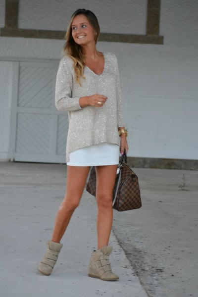 Pink V-neck sweater with a relaxed fit and a white mini dress
