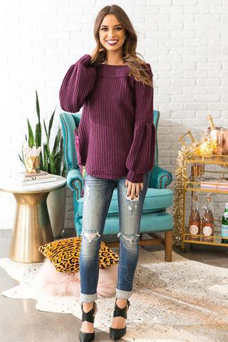 purple ribbed boat neck sweater and ripped jeans