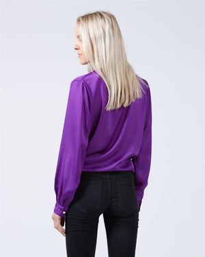 purple shirt with puff sleeves and dark blue skinny jeans