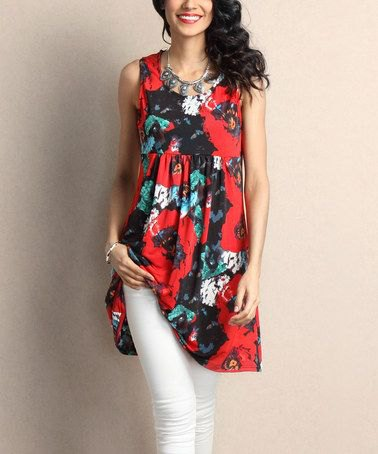 red and black tunic top with floral pattern and white skinny jeans