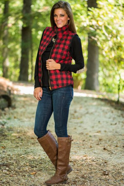 red and black checked vest with mock neck and brown knee-high leather boots