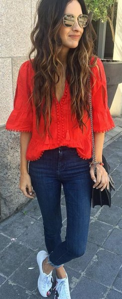 red blouse with V-neckline and dark blue skinny jeans