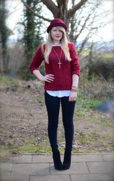 red cable knit sweater over white shirt and black felt hat