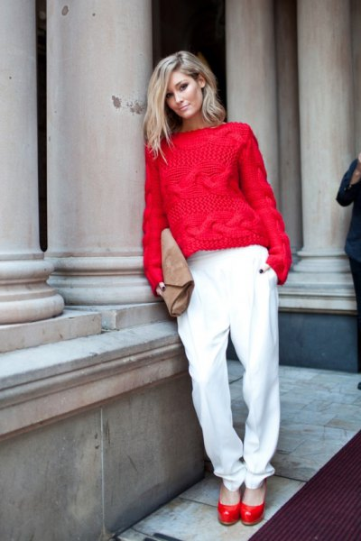 red cable knit sweater with white trousers with a relaxed fit