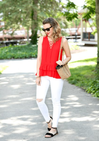 Red sleeveless blouse with a V-neckline and white ripped front with white jeans